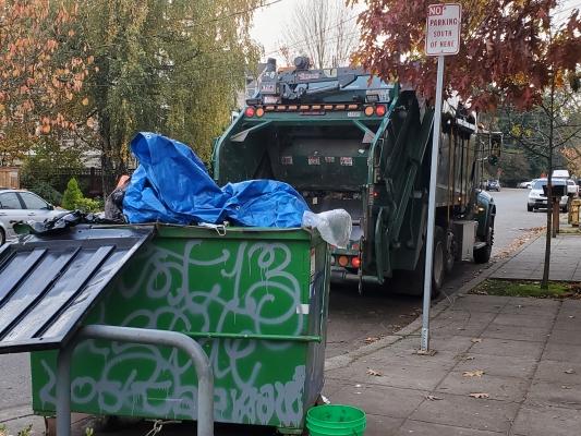 A trash truck outside of Albert Davis Park prepares to empty a full trash receptacle Nov. 9. Photo by Ashley Archibald