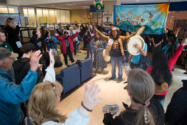 Paul Cheoketen Wagner leads a song in the lobby of the Chase branch located at Third Avenue and Union  Street as indigenous organizers and environmental activists protest funding of the KXL Pipeline. Photo by Alex Garland