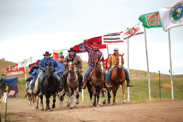 Members of the Cheyenne River Sioux tribe ride along the more than 200  tribal flags that were posted at the protest. Photo by Alex Garland