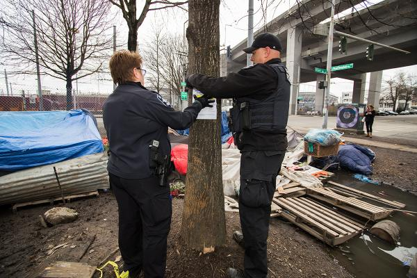 Two police officers post a notice with information about the upcoming sweep of the Field encampment in SoDo. Photo by Matthew S. Browning