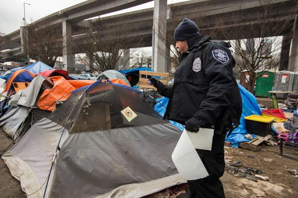 """A Seattle Police officer photographs a tent in an encampment called """"Field of Dreams"""" in 2017. Officers associated with the Navigation Team are required to post notices of removal three days prior to a cleanup in most circumstances in order to give people"""