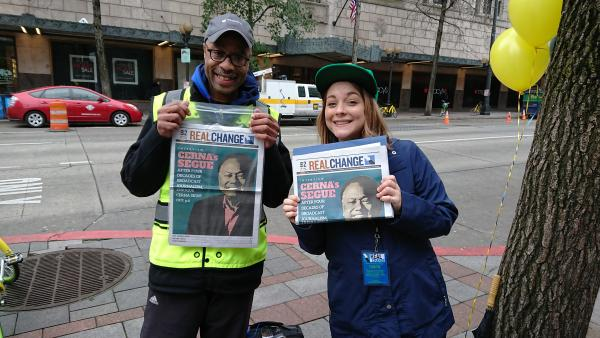 Hanna Brooks Olsen selling Real Change with Glenn Walker. Photo by Lisa Edge