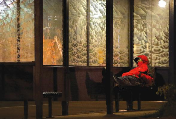 A person finds shelter at a bus stop in the International District when temperatures dip in the low 40s. File photo by Ted Mase