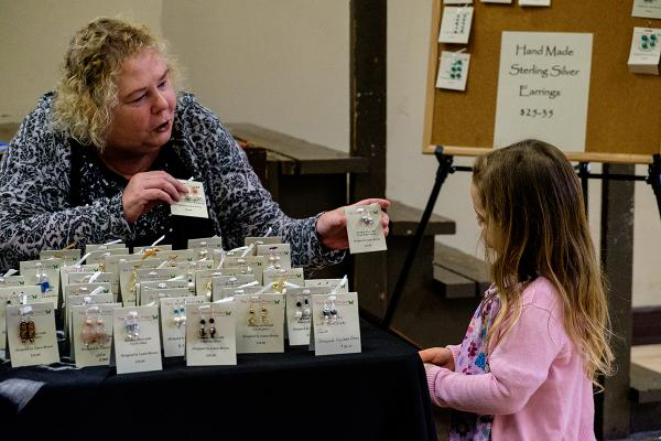 Laura shows a girl a pair of the earrings she made at St. Joseph Church in Seattle. Photo by Alex Bergstrom