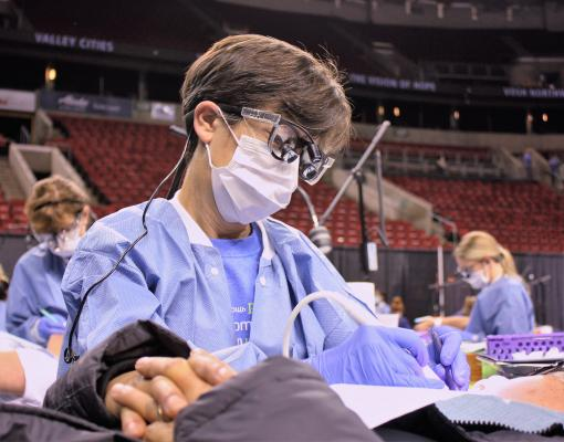 Diane Daubert, of the UW School of Dentistry faculty works on a patient. Photo by Steve Steinberg