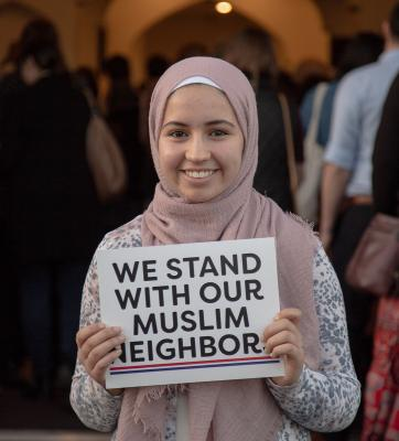 Ihssane El Yacoubi hands out signs at the entrance of The Muslim Association of Puget Sound in Redmond. Photo by Matthew S. Browning
