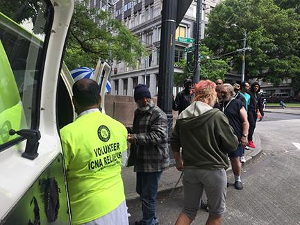 A Mercy on Wheels volunteer hands out food to homeless people on Third Avenue. The program is run by local Muslim volunteers. Photo by Hannah Myrick