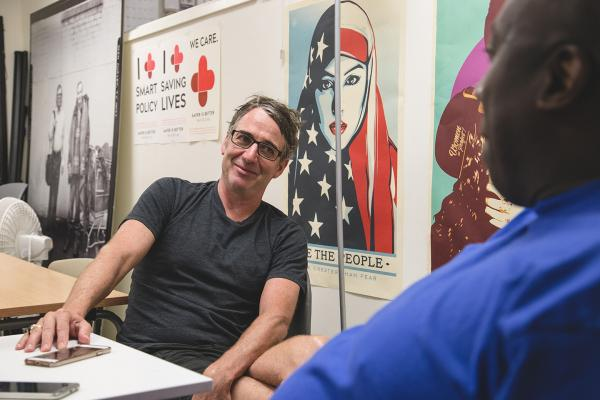 Pearl Jam's Stone Gossard is interviewed by Real Change vendor Darrell Wrenn (right). Photo by Matthew S. Browning