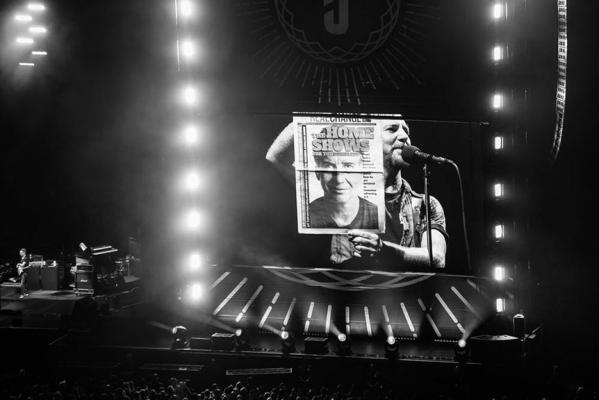 """On Aug. 10, Eddie Vedder of Pearl Jam told concertgoers """"but this is a cover that really means something"""" while holding up a copy of Real Change with guitarist Stone Gossard on the cover at Safeco Field. Photo by Charles Peterson"""