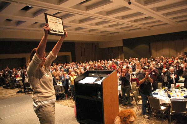 Lisa Sawyer holds her award to a standing ovation