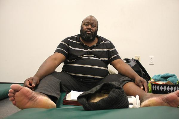 Charley Martinear sits on his mat reading his Bible before lights go out in the shelter at 8:30 p.m. The shelter opens at 7 p.m., and residents must leave by 7 a.m. the next morning.