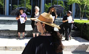 Women in Black participants stood outside of the Seattle Municipal Court in the hot sun Aug. 24 to mourn the deaths of two homeless people killed in Kent in August. Photo by Aaron Burkhalter, Real Change