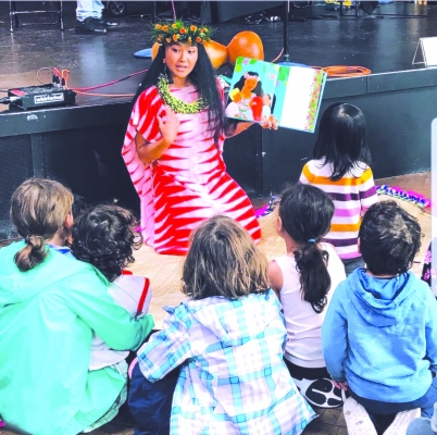 Matsui reads a picture book aloud during a 2018 Northwest Folklife Festival program at Seattle Center.