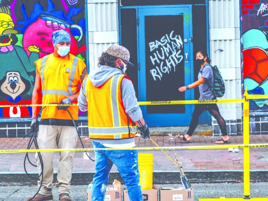 "Dahvee Enciso, who works for SDOT and is experienced with street painting, offers support to the artists in the second, more permanent painting of ""Black Lives Matter."" Photo by Mark White"