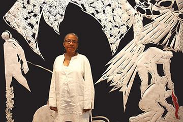 """Seattle Artist Barbara Earl Thomas stands near a 2016 piece titled """"Blood Catcher,"""" an installation at the Bainbridge Island Museum of Art. Her show runs through Oct. 2."""