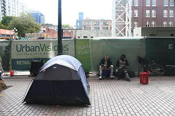 Homeless campers gather in Occidental Park surrounded by the construction of the Weyerhaeuser corporate office. File photo by Jon Williams, Real Change