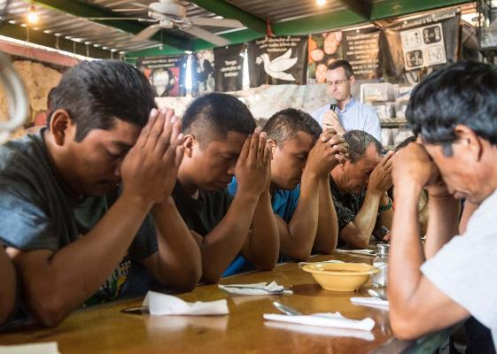 Migrants pray before a meal at El Comedor in Nogales, Mexico. Photo by Larry Hanelin.