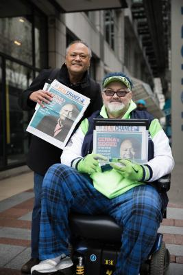 Broadcast journalist Enrique Cerna works with longtime Real Change vendor David Williams during the International Network of Street Papers Vendor Week celebration last month. Photo by Sam Holman