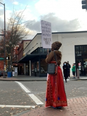 Dione Lucero posts up across the street from Geraldine's; Lucero frequently brings her red wagon, mic and signs to protest on sidewalks or amid crowds. Photo by Lee Nacozy