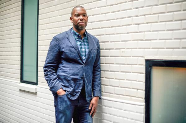 Journalist Ta-Nehisi Coates standing in a hallway, leaning against the wall.
