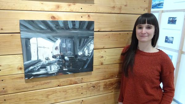 "Artist Laura Hamje stands next to ""Puddle I,"" one of 53 painting depicting the Alaskan Way Viaduct at Bryan Ohno gallery. Photo by Lisa Edge"