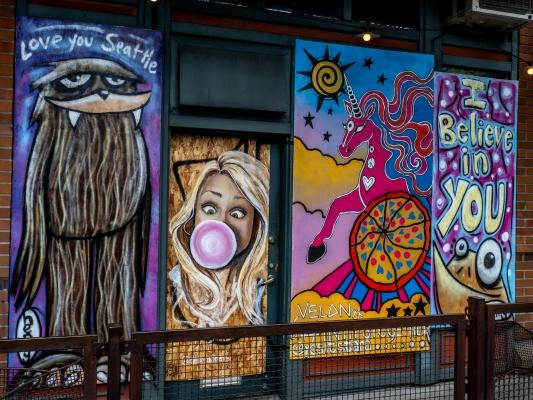 Belltown Pizza displays the varied styles of Seattle muralists including Ryan Henry Ward.