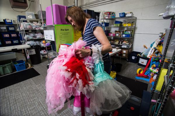 Volunteer Debbie Thoma sorts through donated dresses at Westside Baby in White Center. Photo by Matthew S. Browning.