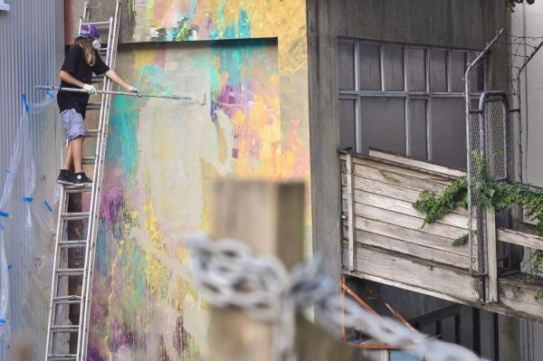 An artist from New Zealand, who will exhibit in the show, works on removing graffiti from a building.