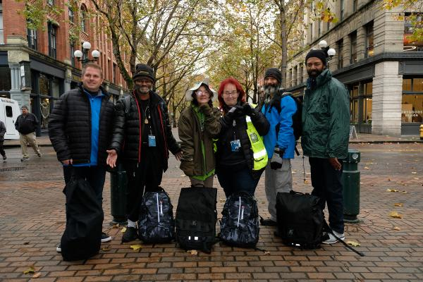Real Change vendors model warm clothing collected by Survive the Streets in Occidental Park. Photo by Valerie Franc-Houge