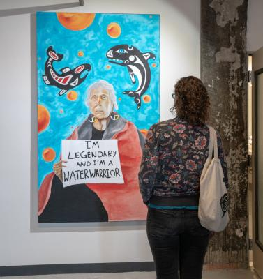"A visitor views ""Ode to Ramona Bennett"" by Taylor Dean (Puyallup), acrylic on canvas, 2018. Photo by Jeff Few."