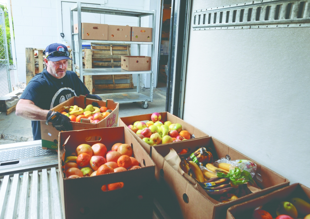 A volunteer for We Don't Waste in Denver organizes their food stock and prepares for visitors from their surrounding community. Photo courtesy of We Don't Waste