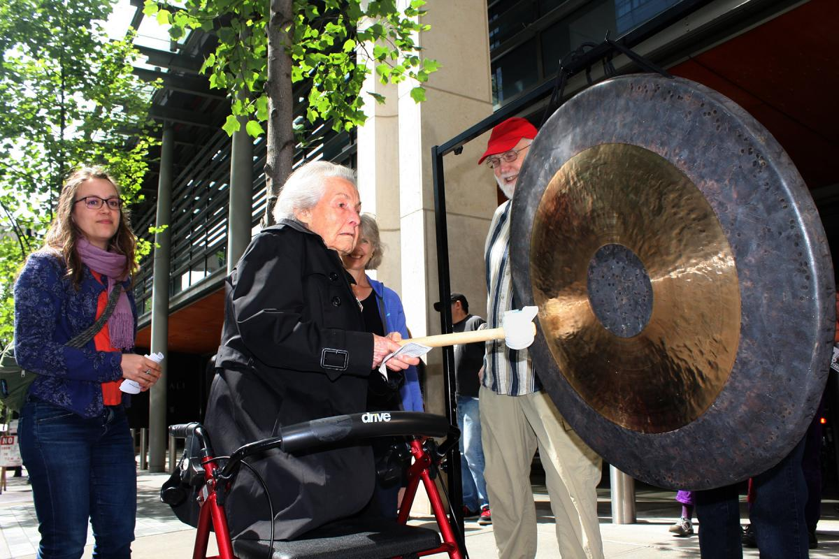 Life-long activist Dorli Rainey, 91,  above, takes her turn sounding the gong in front of Seattle City Hall June 12. Photo by Jon Williams