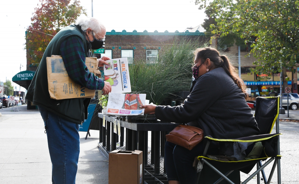 Jay Wang of Seattle buys a Real Change newspaper outside of the Wallingford QFC on 45th Street. Lopez was homeless for 13 years and has been a Real Change vendor for six years. She plans to move into an apartment by December and continue to build strong r