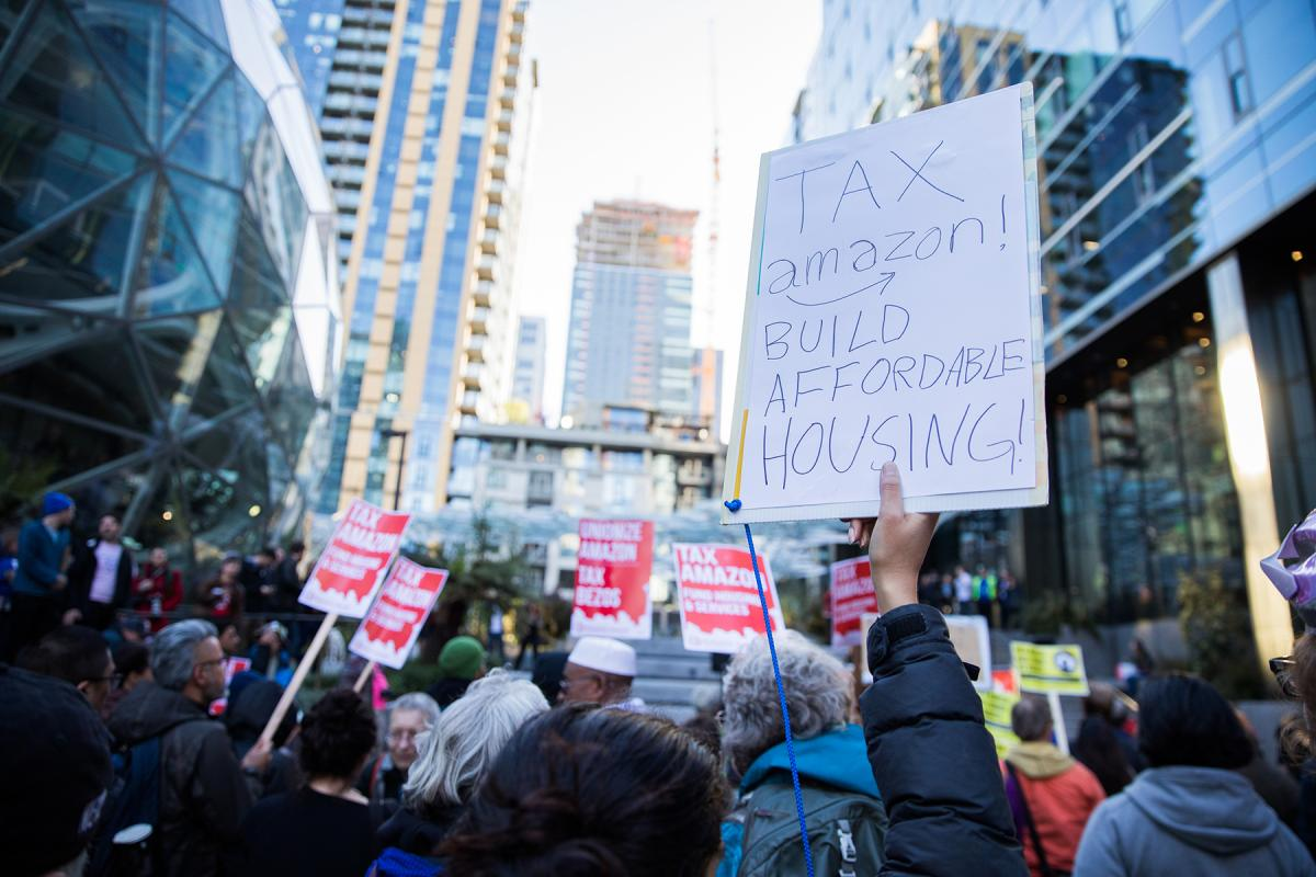 Dwarfed by the Amazon Spheres and additional buildings connected to the sprawling campus, protesters gather to rally for new taxes on large businesses in Seattle to pay for affordable housing. Photo by Alex Garland