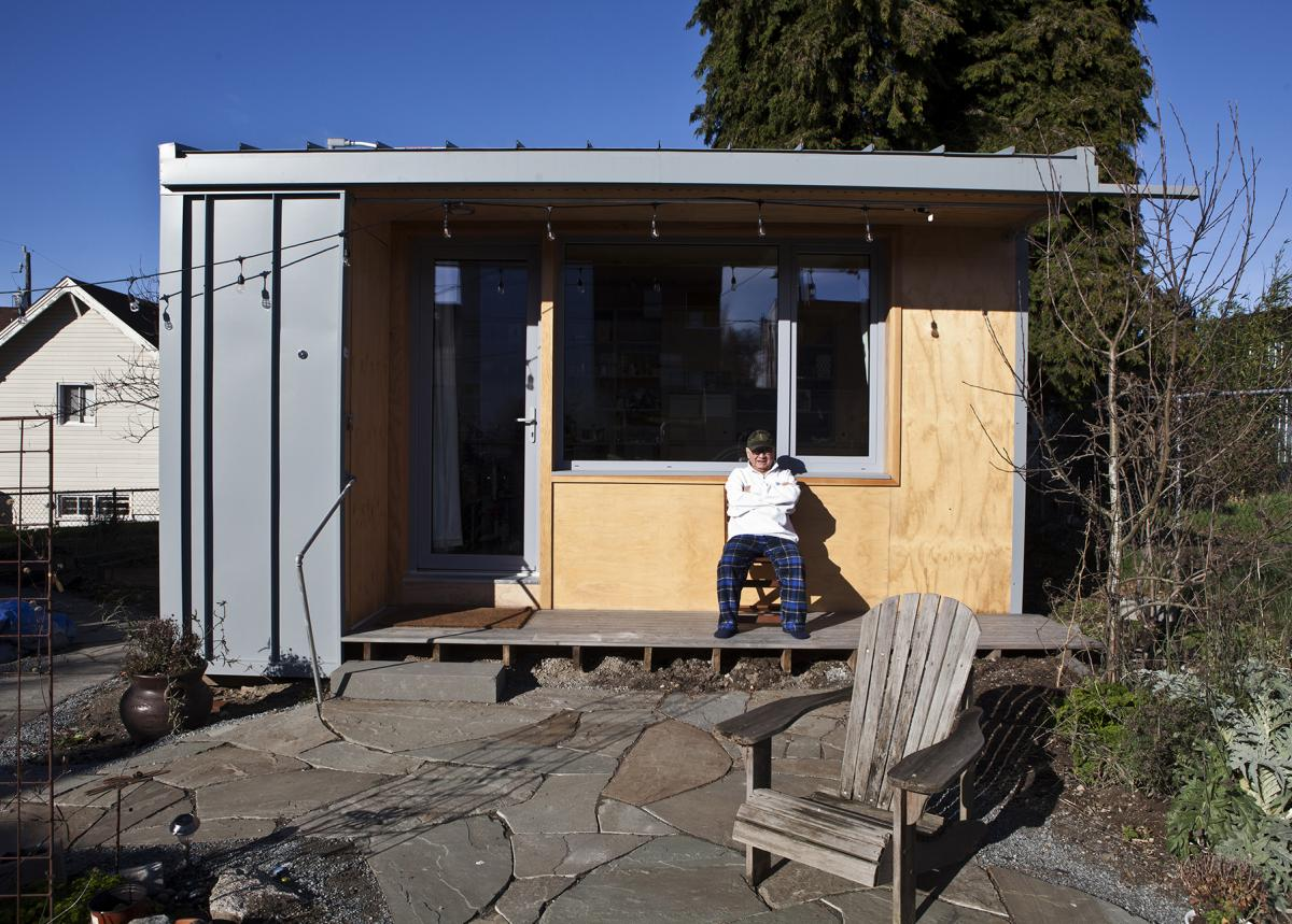 Bobby Desjarlais sits on the porch of his 125-square-foot cottage located in the backyard of a Beacon Hill home. Photo courtesy of Facing Homelessness