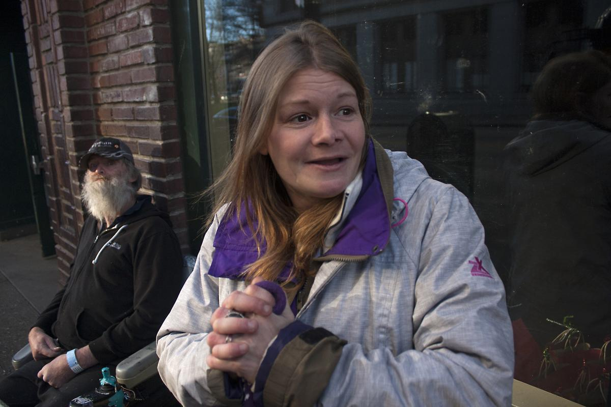 Carrie Clark tells her own story of homelessness, involving domestic violence, in front of DESC. Photo by Jon Williams