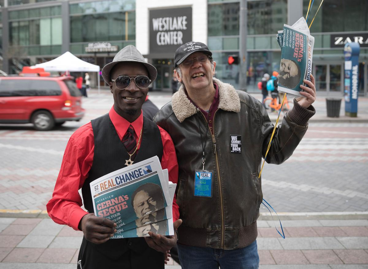 Founding Director Timothy Harris (right) sells copies of Real Change alongside vendor Darryl Manassa (left) for vendor week during Feb. 2018. Photo by Sam Holman