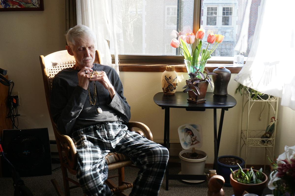 Robert Fuller sits in his apartment on Capitol Hill, contemplating his rosary. Photo by Wes Sauer