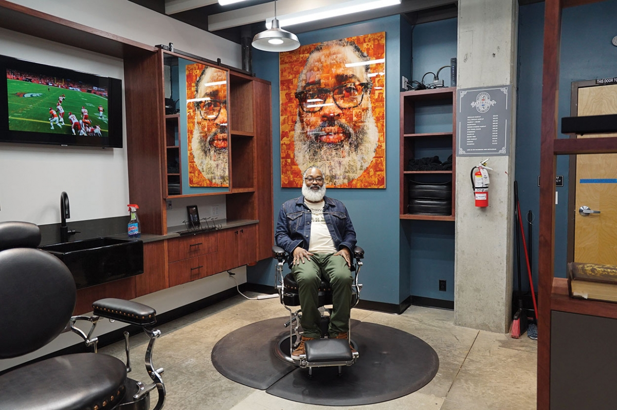 Earl Lancaster, of Earls Cuts N Styles Barbershop, sits in a barber chair at his new shop at the Liberty Bank Building in the Central District. Photo by Susan Fried