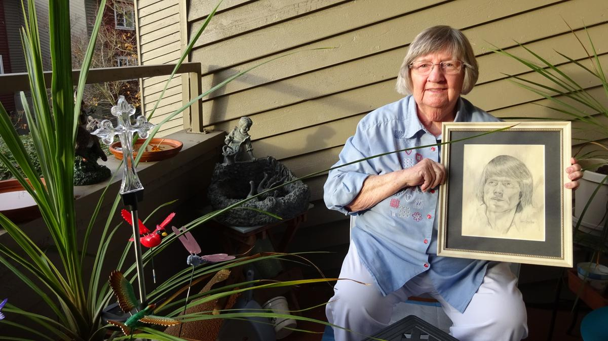 Frances Davis holds a drawn portrait of her son Donald Schultz. Photo by Lisa Edge