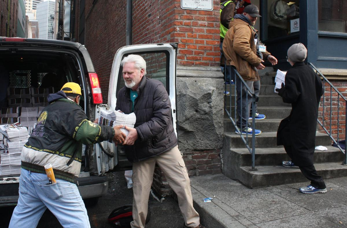 Vendor George Sidwell, center, helps unload new Real Change editions in March. Photo by Jon Williams
