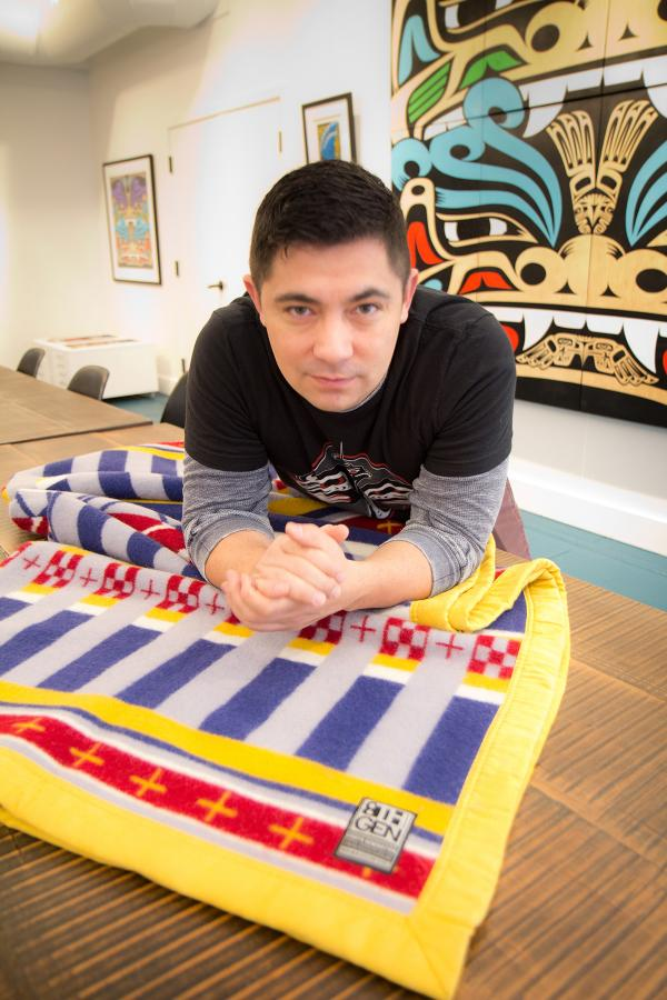 Louie Gong, owner of Eighth Generation, with one of the wool blankets he sells at his store in Pike Place Market. Photo by Wes Sauer