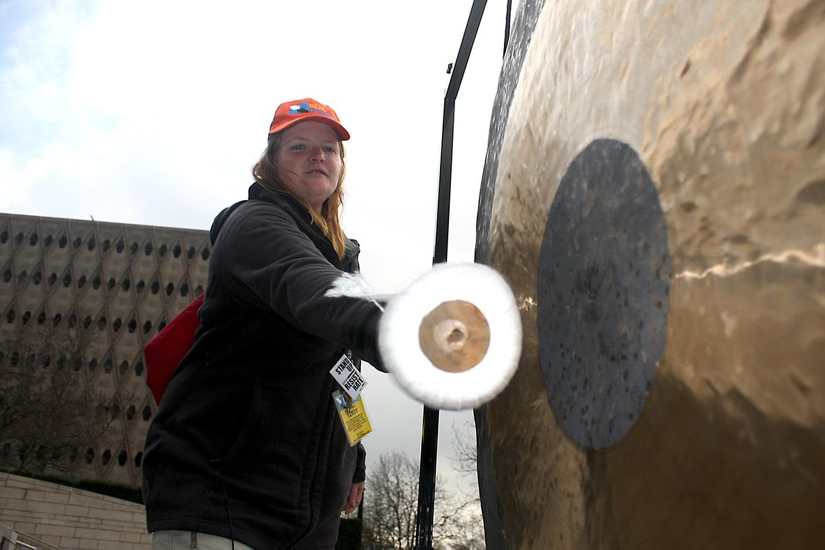 Vendor Lisa Sawyer bangs a gong to raise awareness of homelessness at City Hall in January 2017. Photo by Jon Williams