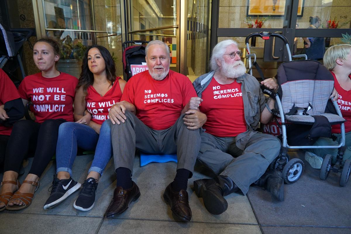 The Reverend Paul Benz, Co-Director of Faith Action Network, center, links arms with other protesters outside ICE headquarters. Photo by Susan Fried courtesy of the South Seattle Emerald