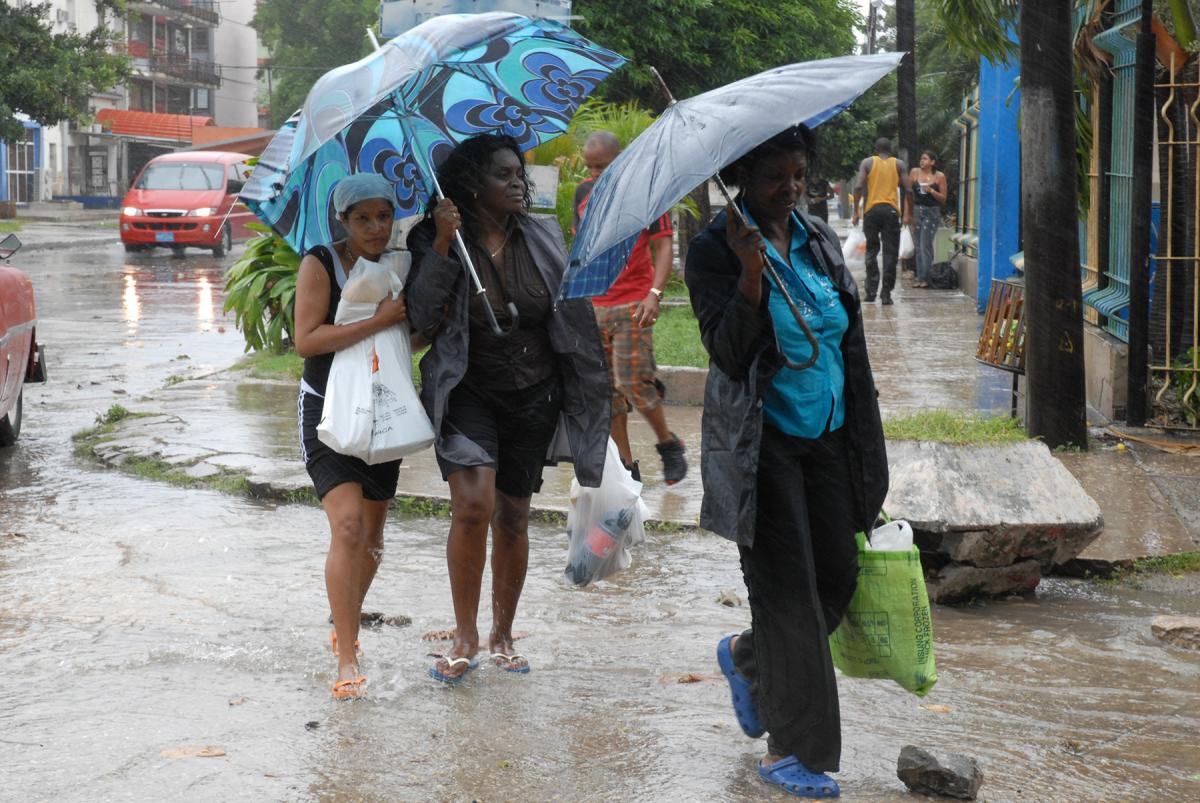 Women walk in the rain carrying food in preparation for the imminent arrival of hurricane Gustav, in 2008 in Havana.