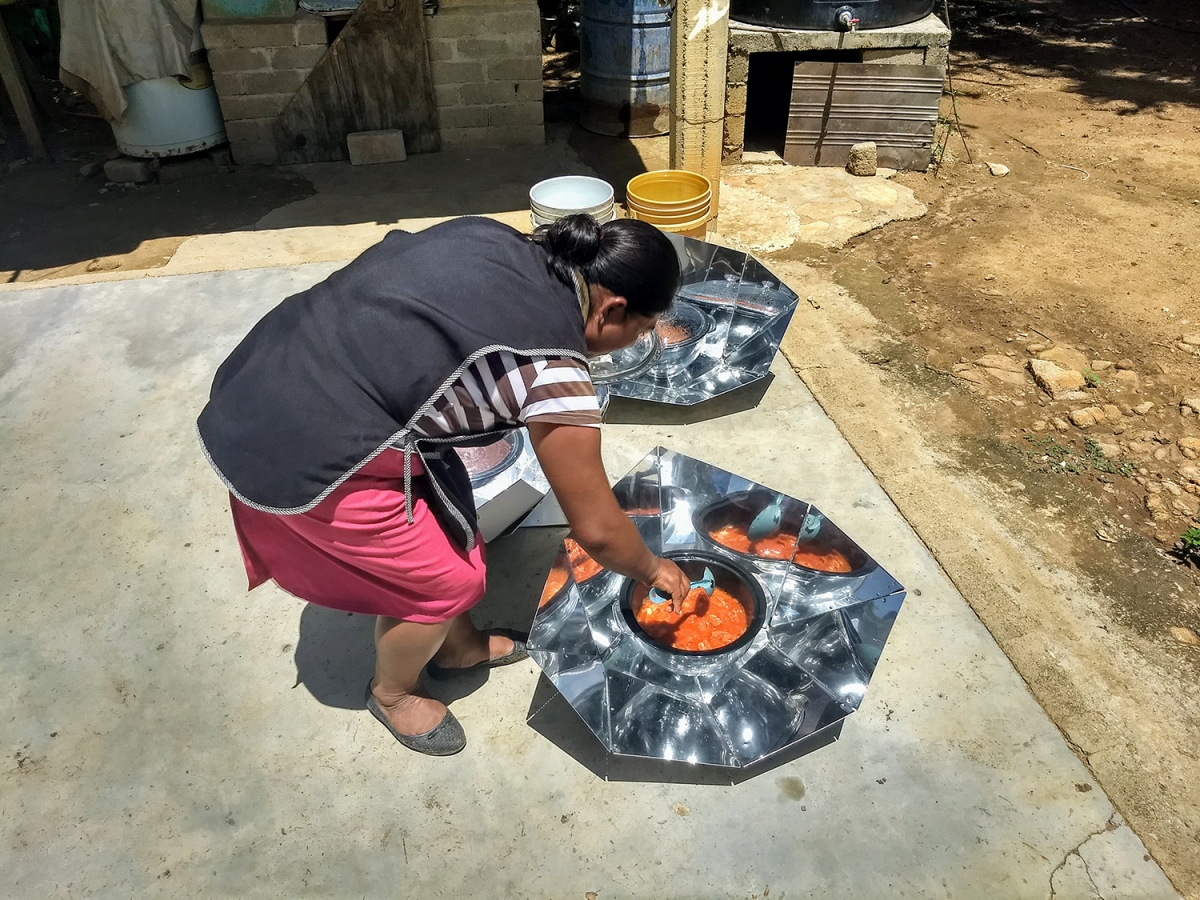 Reyna Díaz checks the marinated pork she is cooking in a solar cooker at her home in a poor neighborhood of Vicente Guerrero, Villa de Zaachila municipality, in the southwestern Mexican state of Oaxaca. The use of solar cookers has made is possible for 20