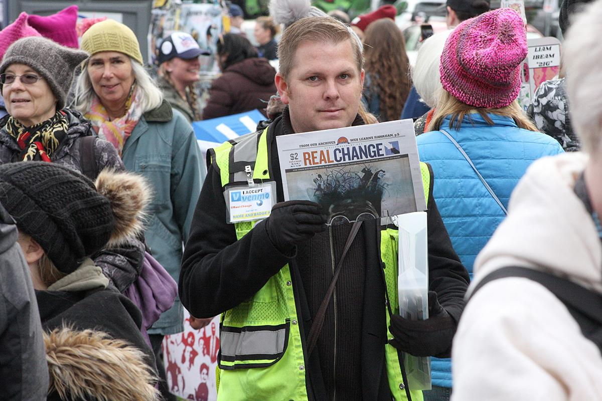 Real Change Vendor James Jenkins selling papers at the 3rd Annual Womxn's March in Cal Anderson Park Saturday, Jan. 19. Photo by Jon Williams