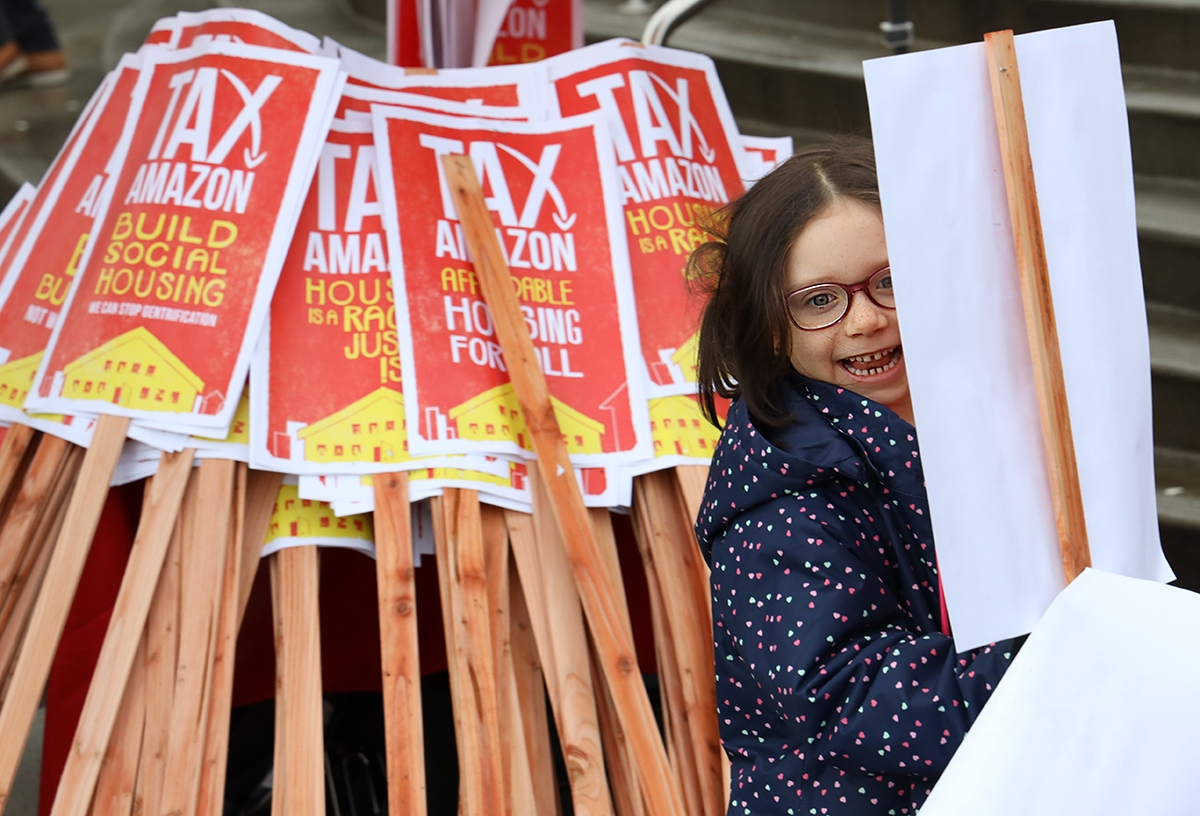 """Six-year-old Vera Lindsey plays with a pile of """"tax Amazon"""" signs at the annual Martin Luther King Jr. March and Rally in Seattle, Jan. 20."""