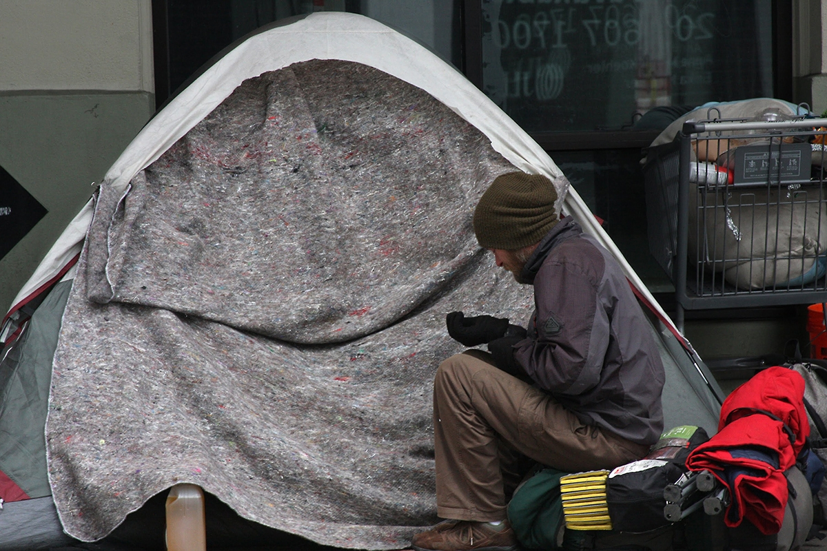 """Sean Struble tries to warm his hands during February's snow storms in downtown Seattle. """"The only time I do shelters is when the police make me. I'll go to a shelter if I have to. But not by choice,"""" said Struble. If you choose to, you can find shelter a"""