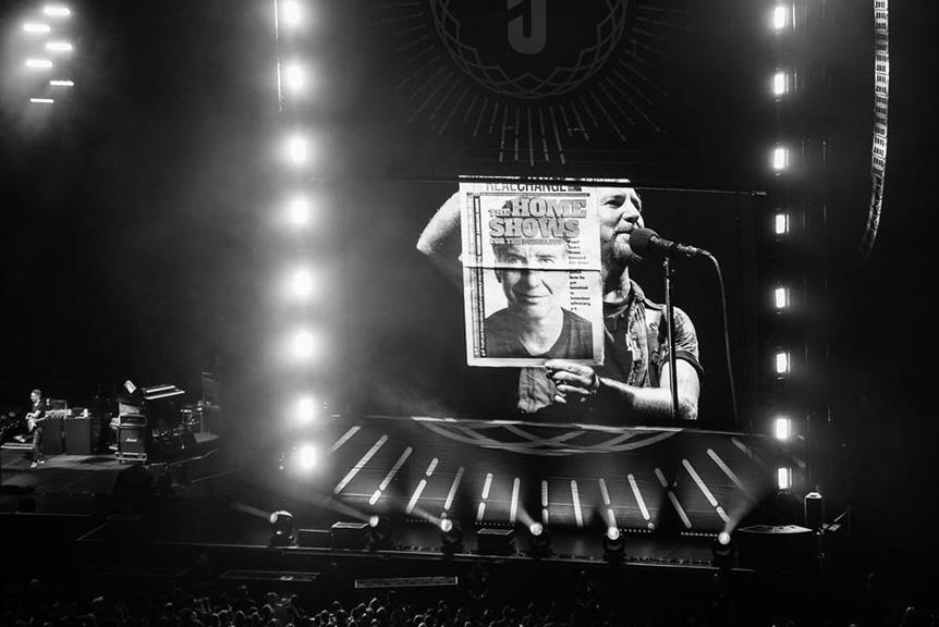 "On Aug. 10, Eddie Vedder of Pearl Jam told concertgoers ""but this is a cover that really means something"" while holding up a copy of Real Change with guitarist Stone Gossard on the cover at Safeco Field. Photo by Charles Peterson"